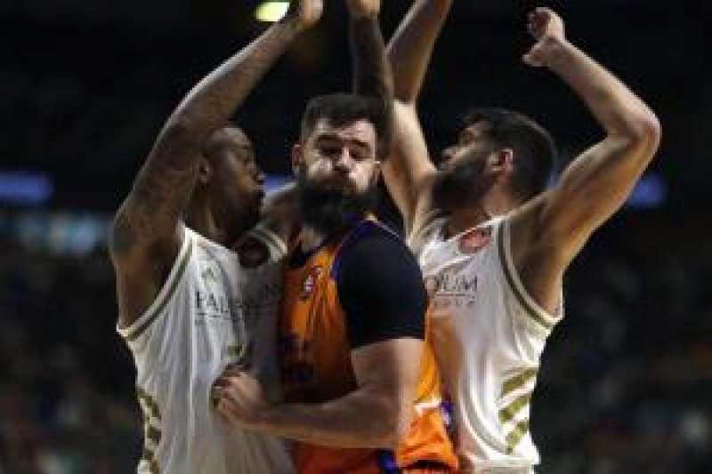 El pívot montenegrino Bojan Dubljevic (c) del Valencia, es bloqueado por los jugadores del Real Madrid. EFE