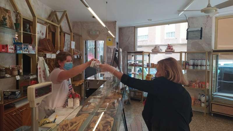 La alcaldesa de Bétera entregando material de protección en un comercio. / EPDA