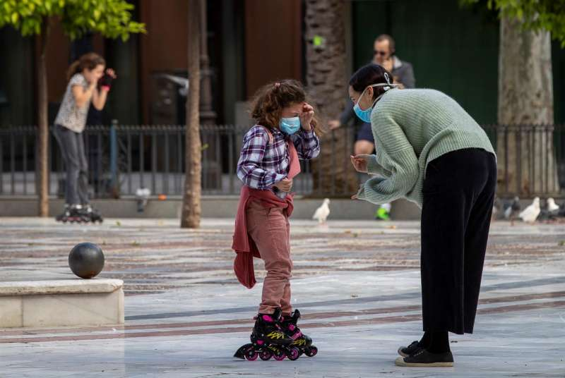 Una niña en patines y con mascarilla conversa con una mujer.