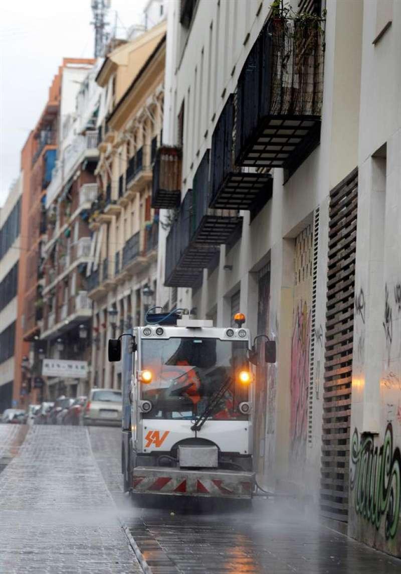 Una máquina de limpieza baldea una calle en València para desinfectar, durante la tercera jornada en estado de alarma por el coronavirus. EFE/Manuel Bruque
