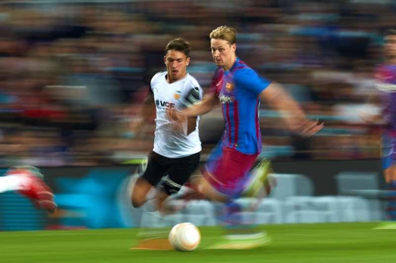 El centrocampista neerlandés del FC Barcelona Frenkie de Jong (d) conduce el balón ante el delantero del Valencia Hugo Duro.