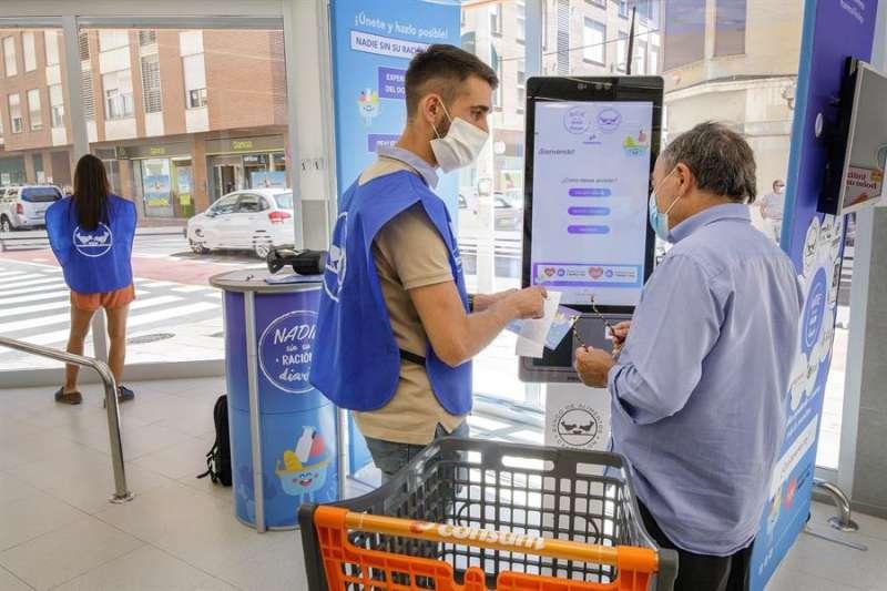 En la imagen un voluntario explica el funcionamiento de la máquina a un donante. EFE/Domenech Castelló