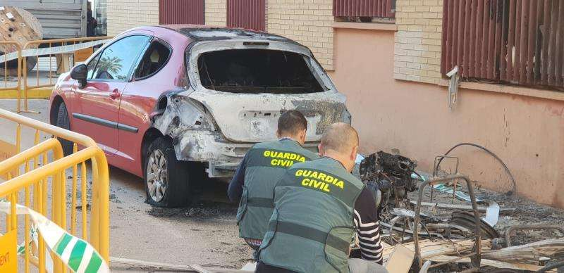 Agentes de la Guardia Civil inspeccionan uno de los coches incendiados en una imagen facilitada por el instituto armado. EFE