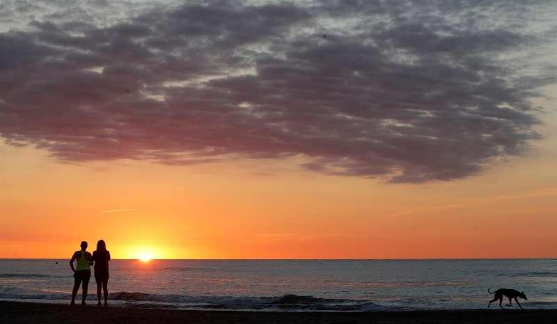 Dos mujeres observan la salida del sol este jueves, festividad de San Juan en la Comunitat Valenciana.