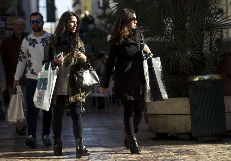 Dos jóvenes con compras pasean por el centro de València. EFE/Archivo