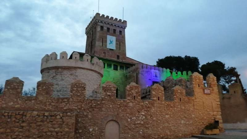 Castell de Benissanó amb la pancarta i els focos verds i morats en homenatge als colors que utilitzen els treballadors de la sanitat. / EPDA