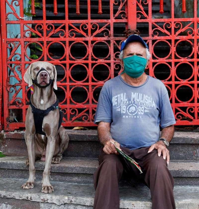 Un hombre mira a la cámara mientras se sienta junto a su perro. EFE