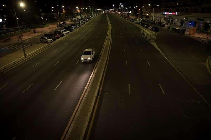 Un coche circula por una avenida de la ciudad de Valencia durante la medianoche.
