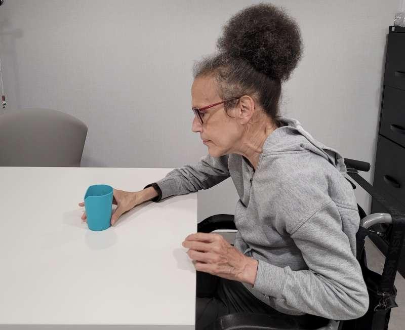 Una mujer se hidrata con un vaso de agua