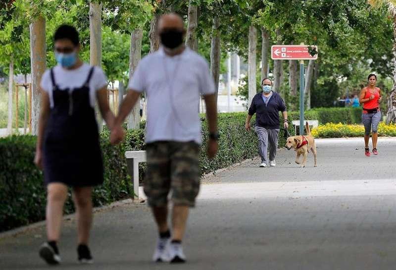 Personas pasean con la mascarilla