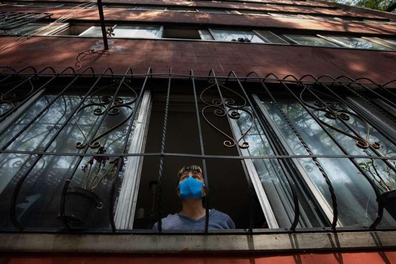 Una persona mira desde su ventana con mascarilla