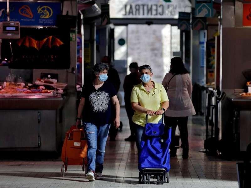 Dos personas realizan sus compras con la mascarilla. EFE