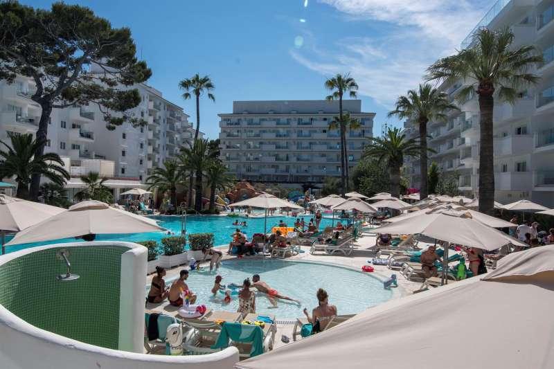 Huéspedes disfrutas de las instalaciones exteriores de un hotel.