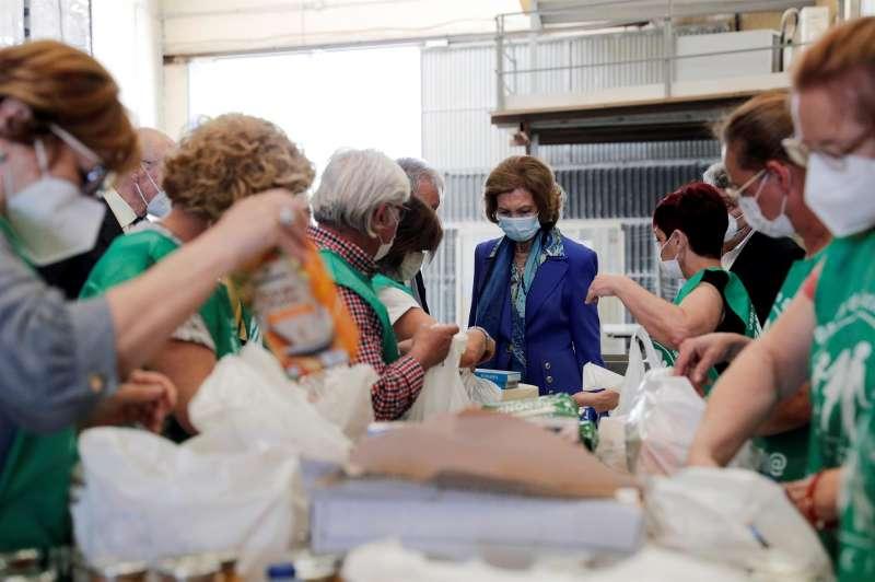 La reina Sofía (c) observa el trabajo de unos voluntarios durante su visita este jueves al Banco de Alimentos de Valencia, ubicado en la localidad de La Pobla de Vallbona.