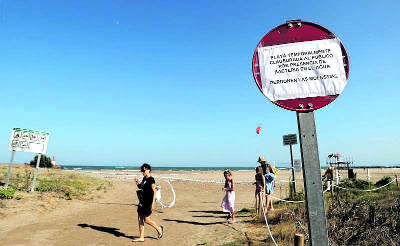Varios bañistas pasan junto a una señal que informa de la prohibición de bañarse en una playa por superar los niveles de bacterias fecales. EFE/Bruque/Archivo