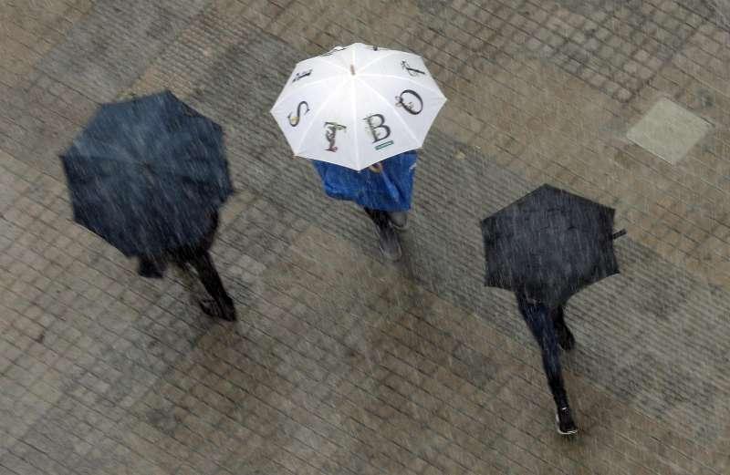 Varias personas se protegen con paraguas de un fuerte aguacero.