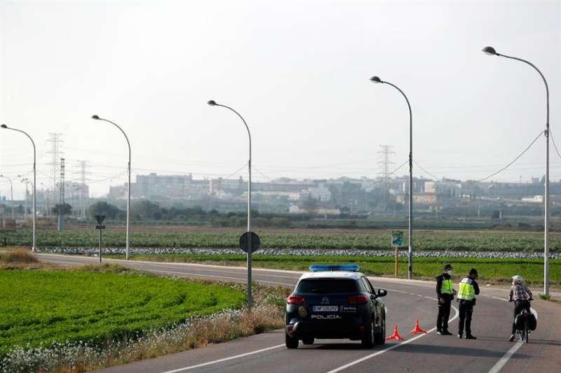 En la imagen, una patrulla de policia nacional para a un ciclista en una de las salidas de Valencia.EFE/Kai Försterling
