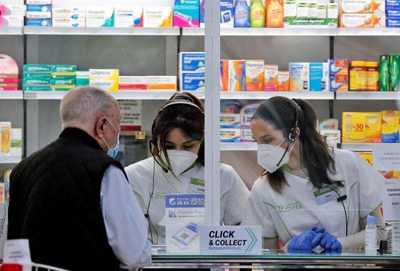Dos empleadas de una farmacia atienden a un cliente. EFE/ Manuel Bruque/