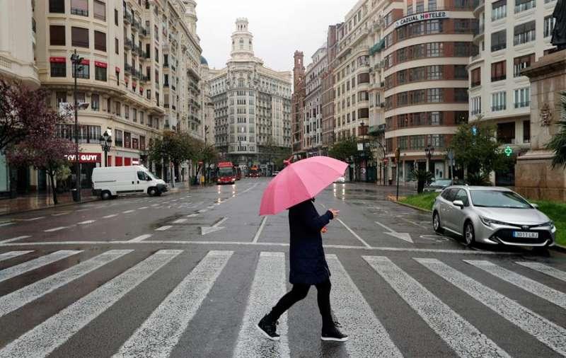 Un hombre protegido con paraguas en la plaza del Ayuntamiento de Valencia en una imagen de archivo. EFE