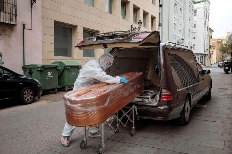 Un operario de la funeraria introduce un féretro en un vehículo de una persona fallecida por covid. EFE/ Biel Aliño/Archivo