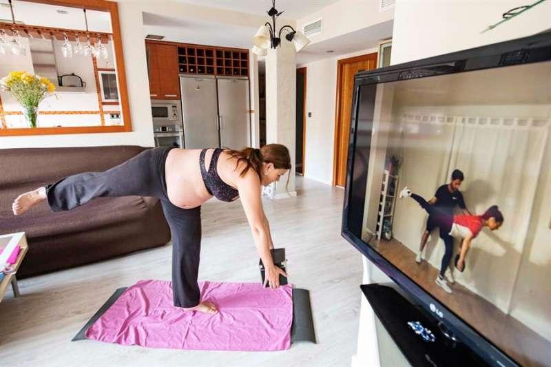 Una mujer embarazada realiza en su casa ejercicios para gestantes impartidos en redes sociales durante el confinamiento. EFE
