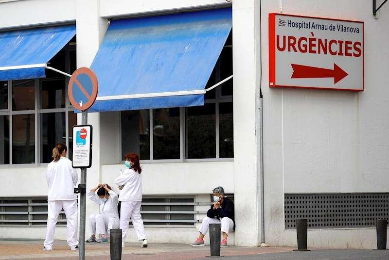 Personal sanitario del Hospital Arnau de Vilanova descansa unos minutos ante la puerta de urgencias. EFE