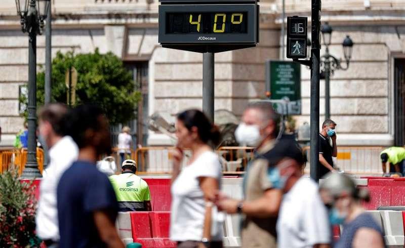 Varias personas pasan ante un termómetro urbano que marca una temperatura de 40º. EFE