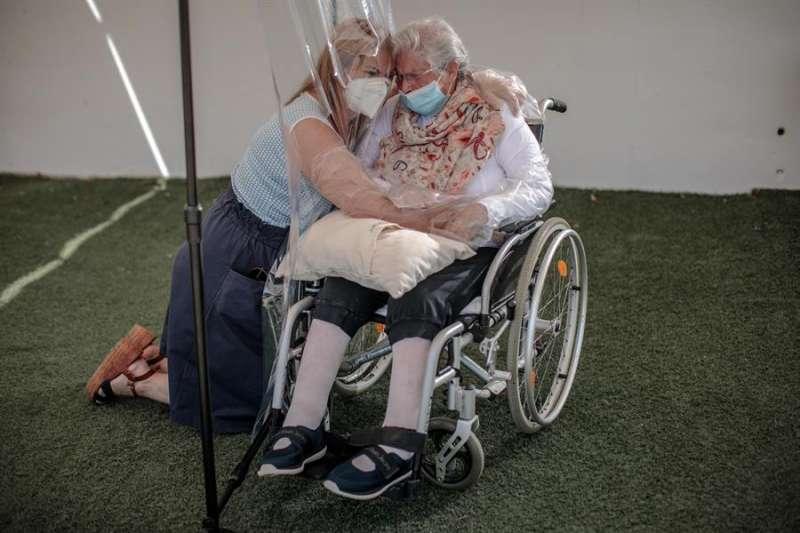 Una interna en una residencia de mayores abraza a su hija a través de un plástico habilitado. EFE