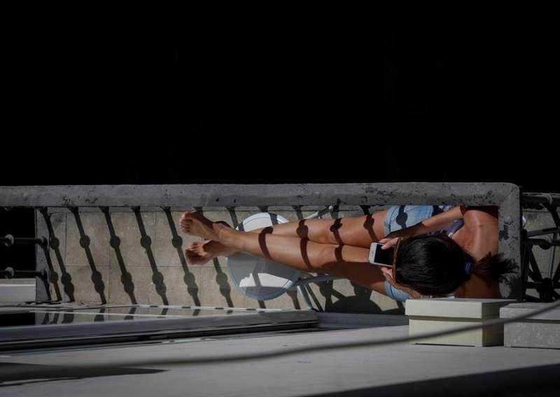 Una joven toma el sol en el balcón de su vivienda durante el confinamiento. EFE