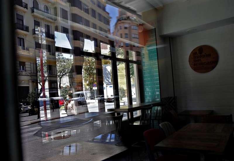 Una joven pasa ante una cafetería cerrada en el barrio del Carmen de València. EFE