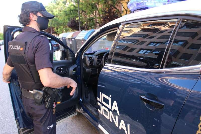 Imagen de un vehículo y un agente de la Policía Nacional.