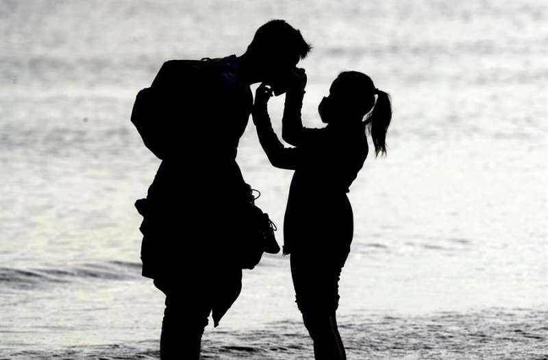 Una joven le ajusta la mascarilla a un joven en la orilla de la playa de la Malvarrosa. EFE