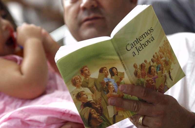 Un padre lee un libro junto a su hija durante una ceremonia de bautismo por inmersión de testigos de Jehová.