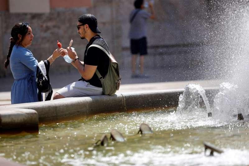Dos personas se toman un helado junto a una fuente.