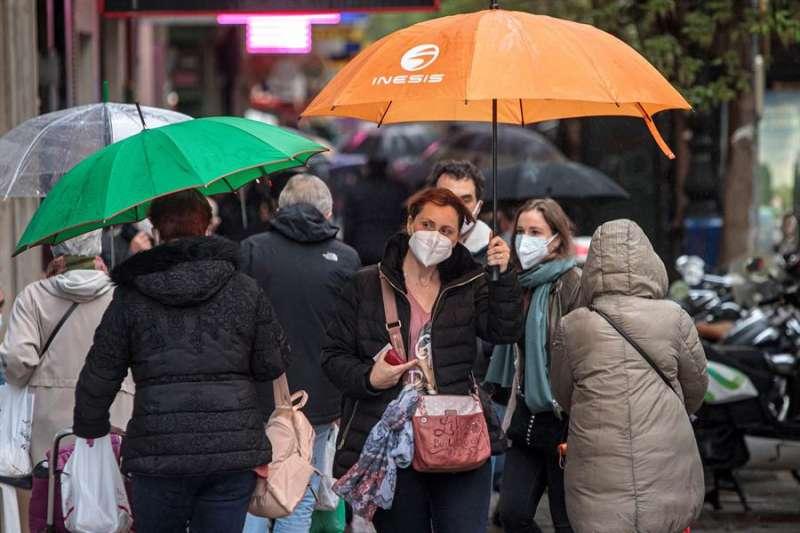 Los ciudadanos se protegen de la lluvia. EFE