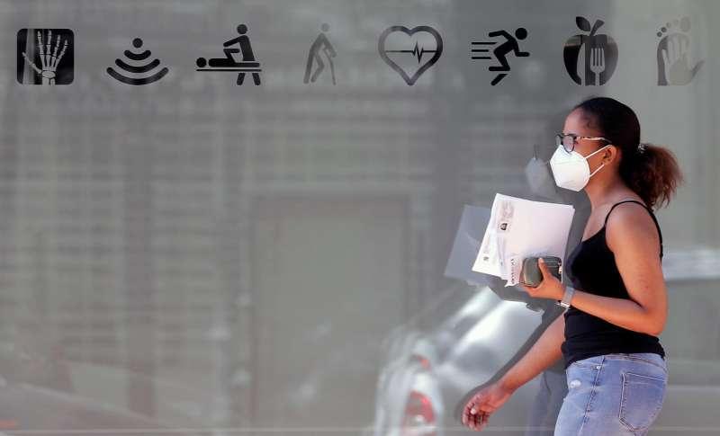 Una joven protegida con mascarilla en una céntrica calle de Valencia