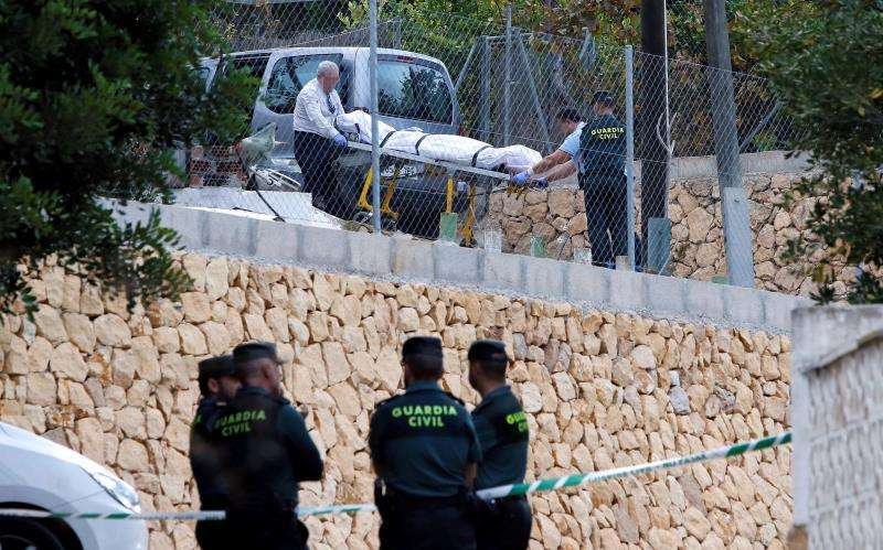 Miembros de los servicios funerarios trasladan el cuerpo de uno de los dos miembros de la pareja sentimental que ha sido hallada muerta por arma de fuego en una vivienda del término municipal de Finestrat (Alicante). EFE