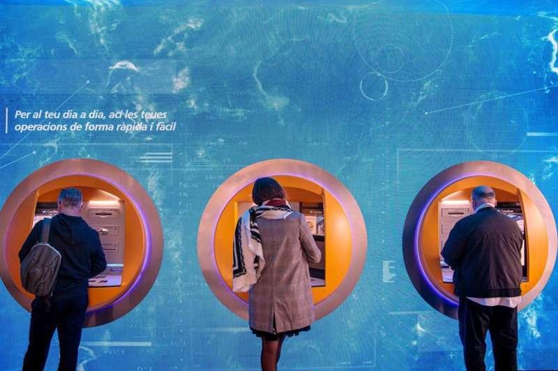 Varias personas operan desde los cajeros automáticos en una oficina de CaixaBank en València. EFE