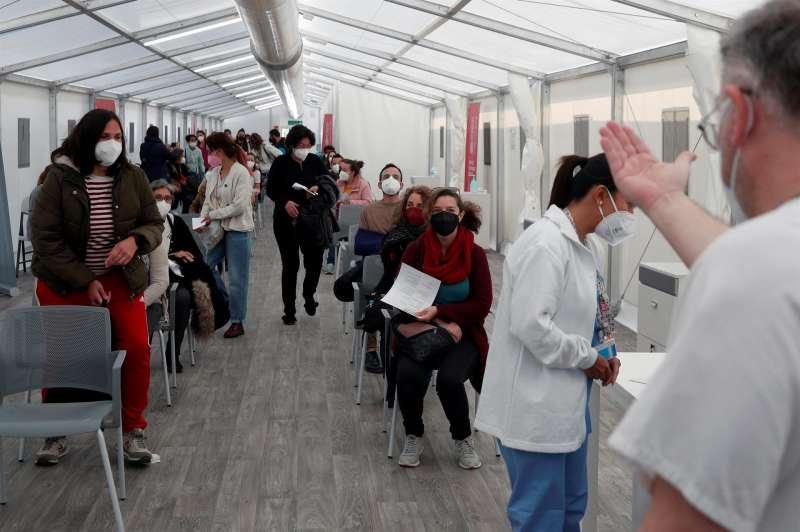 En la imagen, decenas de personas hacen cola para vacunarse.