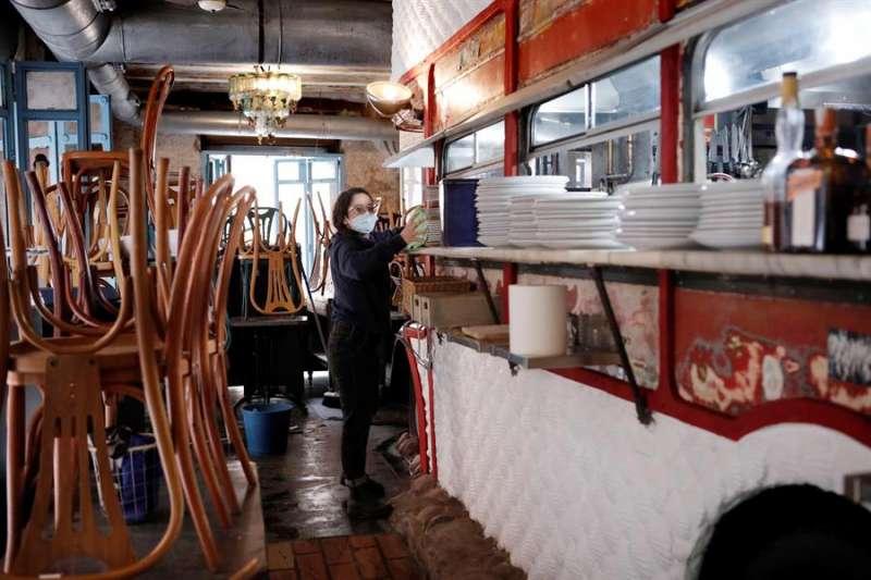 La encargada de un local realiza labores de limpieza y preparación cuando se abrió la hostelería en la Comunitat Valenciana. EFE