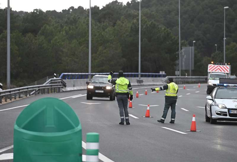Varios guardias civiles de tráfico dan el alto a un vehículo en un control de carretera.