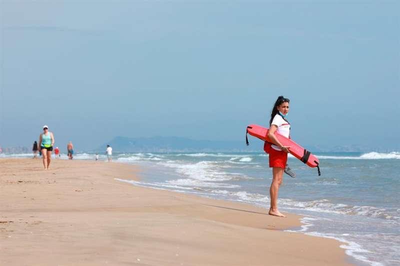 Una socorrista observa a los bañistas en una playa de Gandia. EFE/Natxo Francés