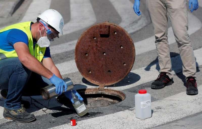 Dos técnicos extraen una muestra de las aguas residuales de la ciudad para ser analizadas. EFE