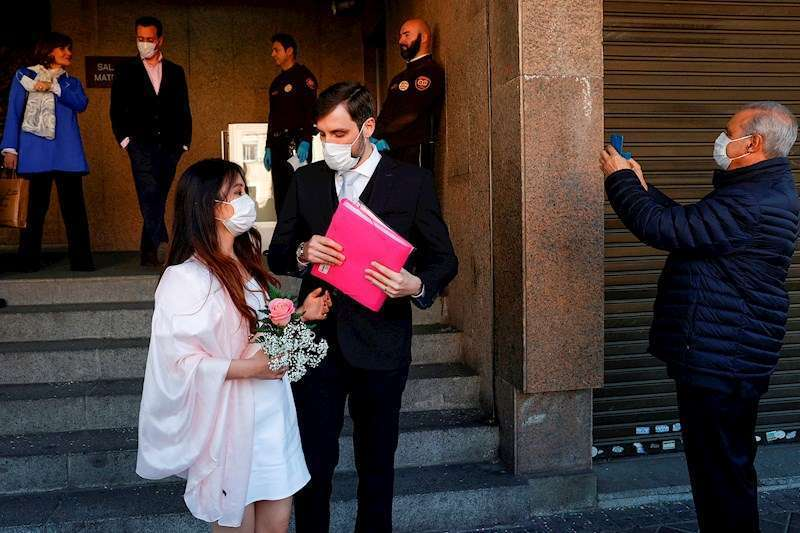 Unos recién casados protegidos con mascarillas salen de una sede del Registro Civil
