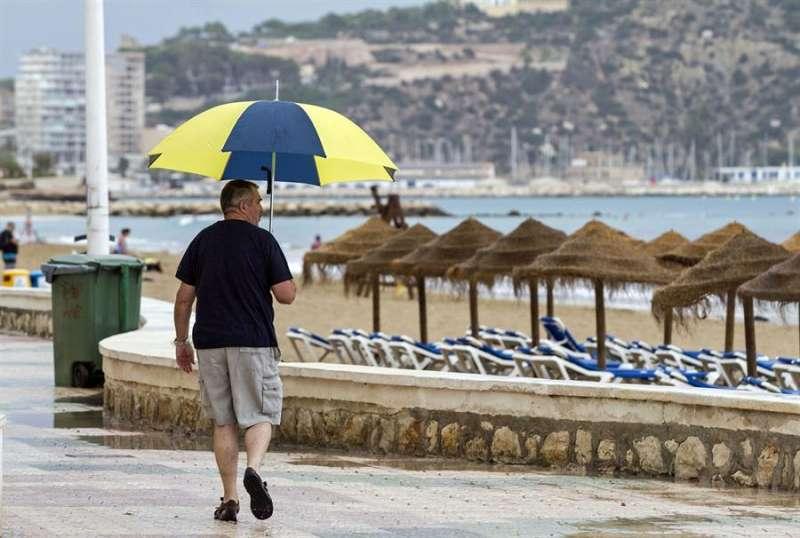 Un hombre protegido camina por el paseo marítimo de Calpe. EFE