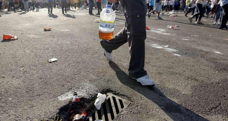 En la imagen, un joven lleva una garrafa de cerveza improvisada, en un botellón en Valencia.