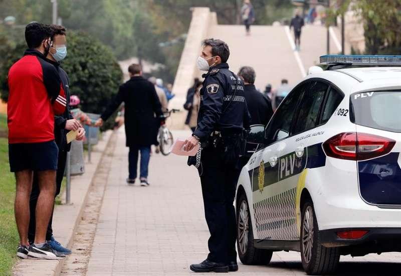 Una patrulla de la Policía Local de Valencia impone sendas multas a dos jóvenes por no llevar mascarilla. EFE