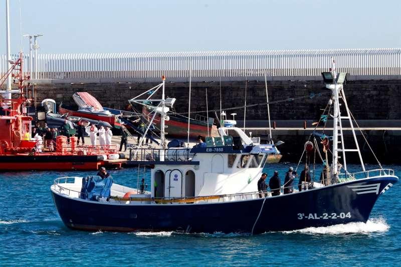 Un barco de pescadores sale del puerto, mientras operarios de una funeraria trasladan el cadáver del hombre