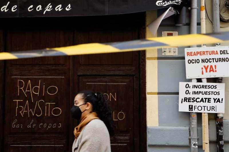 Una persona pasa ante un establecimiento cerrado. EFE/ Ana Escobar/Archivo