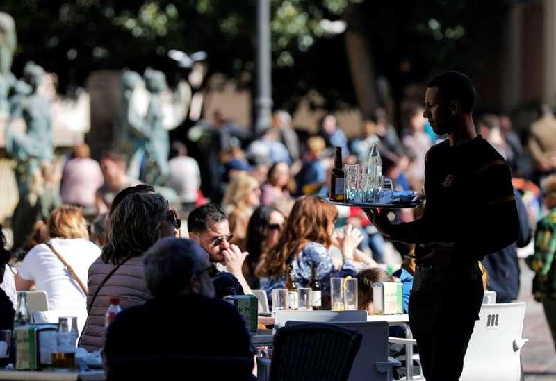 Un camarero atiende una terraza, en la plaza de la Virgen de Valencia, llena de clientes. EFE
